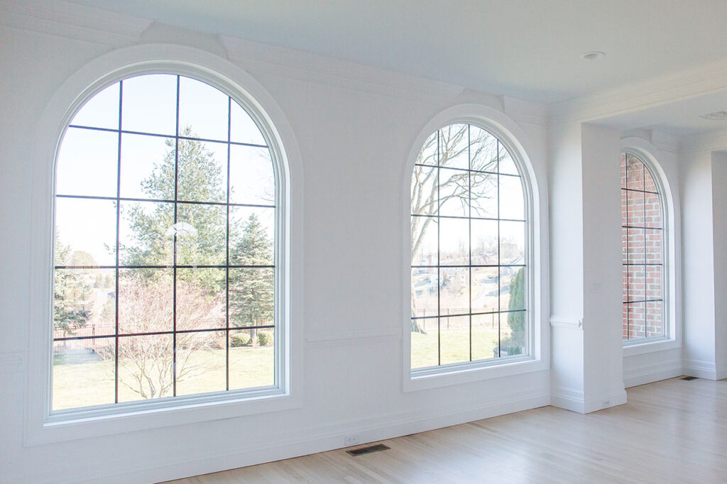 The finished living room windows look great with white trim and black grilles.