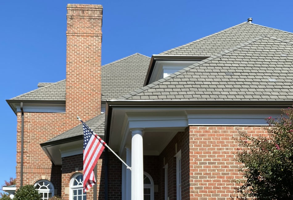 Dark bronze gutters look classic on a red-brick colonial home.